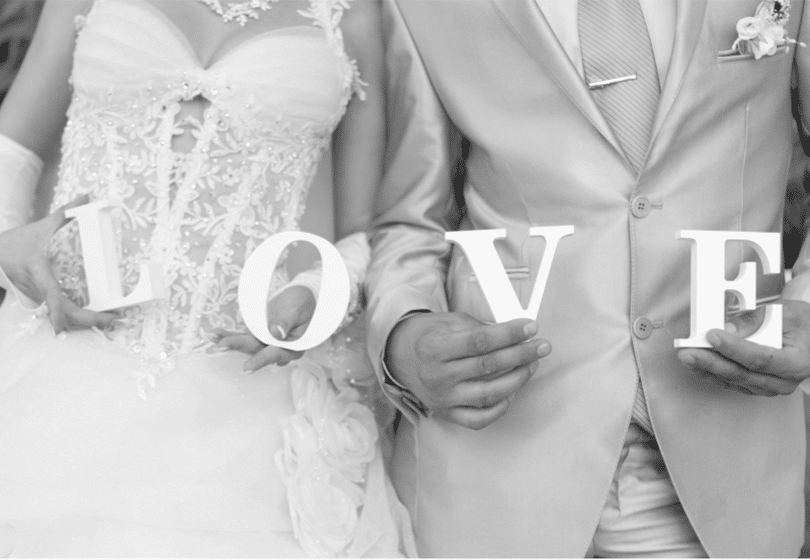 "bride and groom holding letters that spell ""love"""